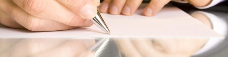 Dłoń trzymająca długopis piszący na białej kartce. W tle druga dłoń.