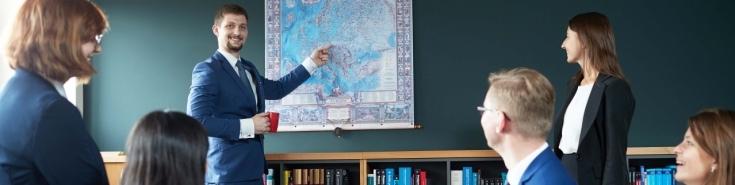 słuchacze KSAP siedzą na kanapach w bibliotece. Jeden słuchacz stoi i pokazuje coś na mapie.