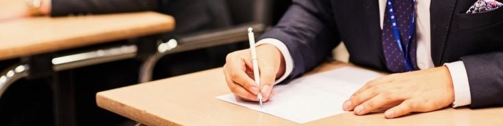 ręka pisząca długopisem na białej kartce leżącej na stole