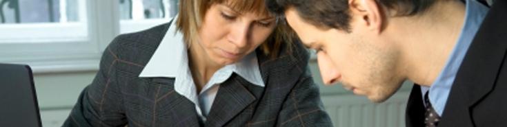 Kobieta i mężczyzna siedzą przy stole i czytają dokumenty