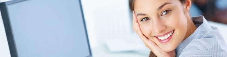 Uśmiechnięta kobieta siedzi przy komputarze
