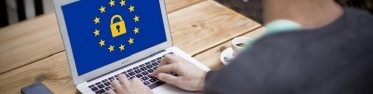 na stole stoi laptop z wyświetloną flagą UE i zamkniętą kłódką. Przy stole siedzi mężczyzna i pisze na laptopie.