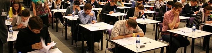 Uczestnicy egzaminu piszą test przy pojedynczych stolikach.