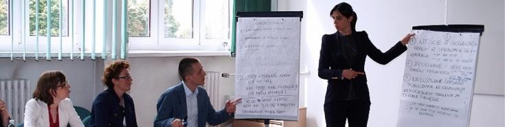 Wykładowca przy flipcharcie tłumaczy trzem uczestnikom szkolenia siedzącym przy stole