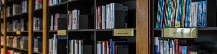 Wcinek zdjęcia przedstawiającego półki z książkami w bibliotece KSAP