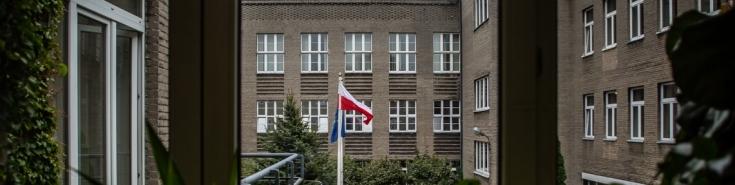Widok z okna na dziedziniec KSAP i powiewające flagi