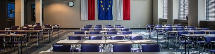 Widok na stoły i krzesła w Auli KSAP na ścianie widać dwie flagi polski i jedna flaga UE