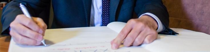 ktoś wpisuje się do księgi gości - widok na same ręce trzymające długopis