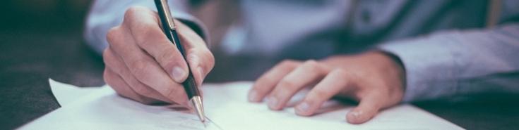 Dłoń trzymająca długopis piszący na białej kartce.