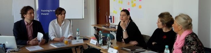 Trenerzy szkoleniowi Programu Erasmus + siedzą w ławkach i dyskutują